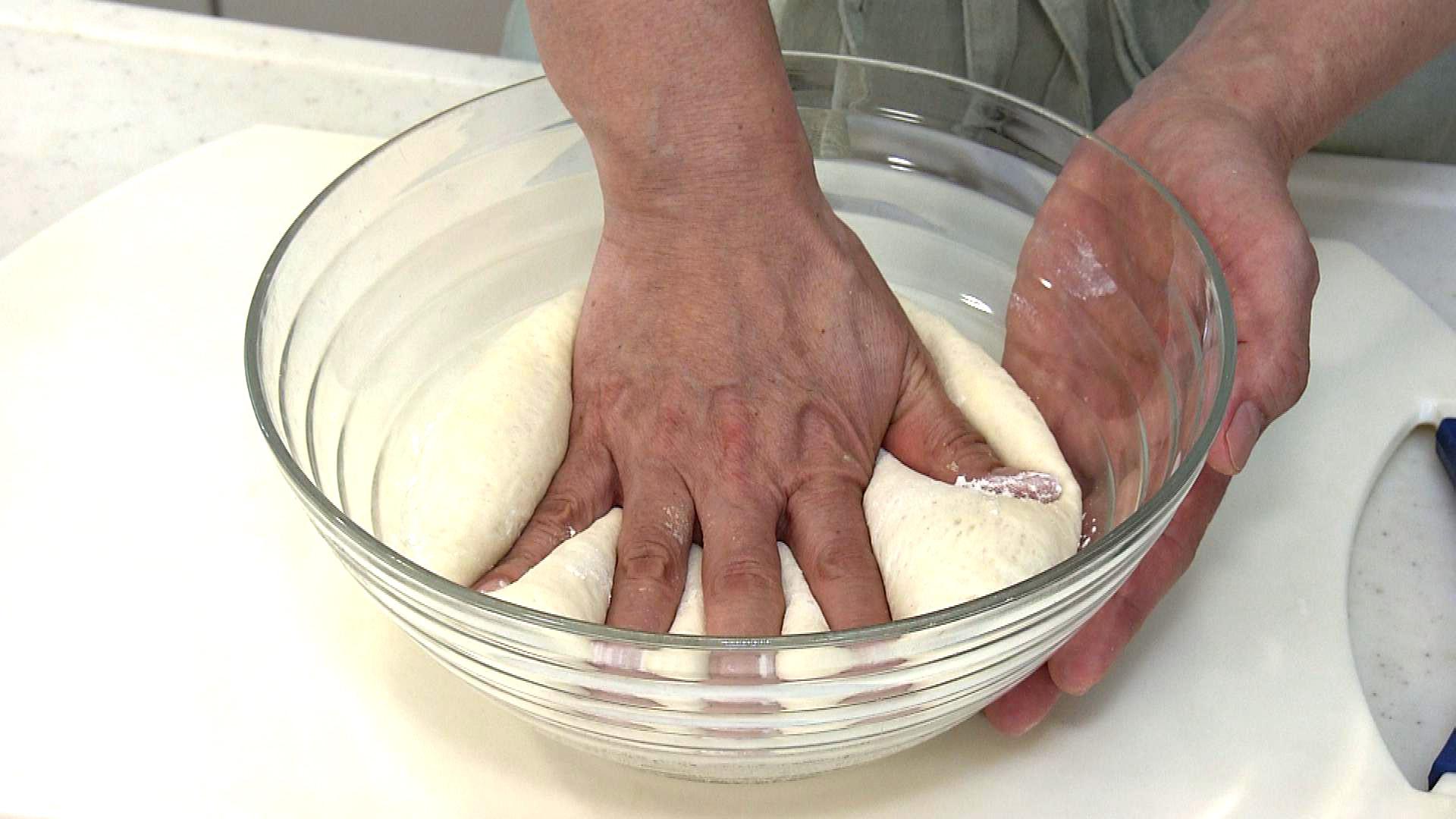 3. 発酵した記事に小麦粉を少しまぶし、手で押さえてガスを抜く。