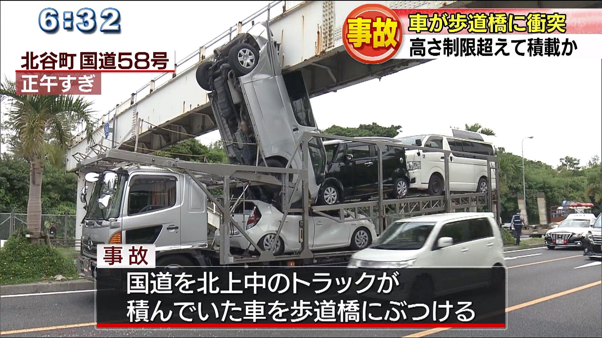 トラックに積んだ車が歩道橋にぶつかる